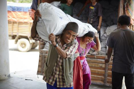 Smiling Nepalese man and woman unload a large tent from a truck