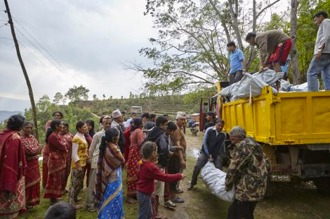 Nepalese villager help unload a truck of Shelterbox aid