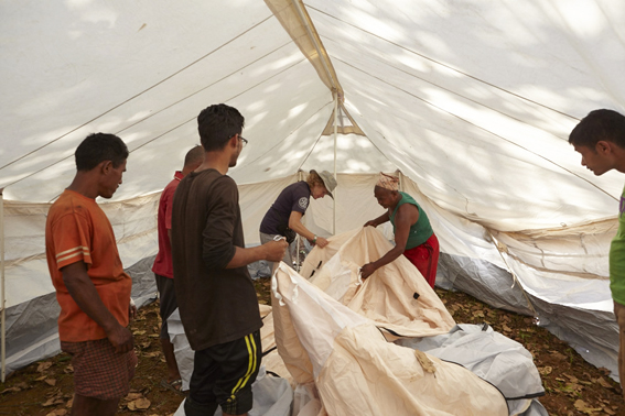 ShelterBox response team member Liz Odell shows villagers in Pipaldanda how to put up the tents that were distributed.