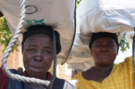 Two women with Shelter Kits balanced on their heads