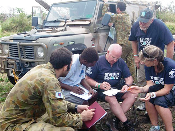Response Team members plan distributions on the ground with the crew of HMAS Tobruk