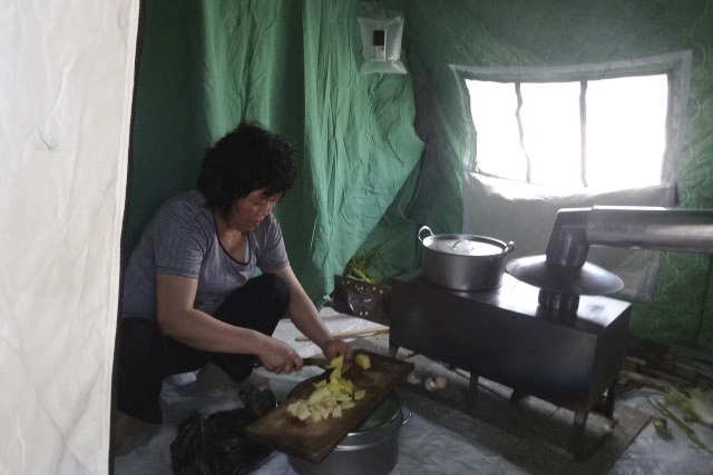 A Korean woman prepares a hot meal on  a wood-burning stove in her Flexi  3 tent