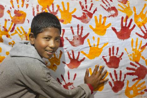 Smiling young Nepalese boy making hand prints with paint on canvas