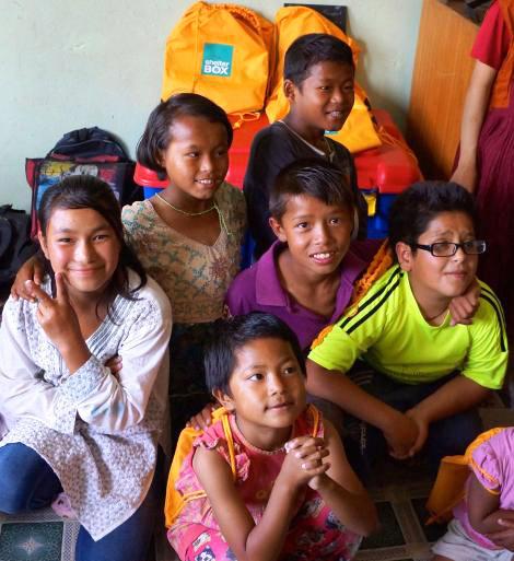 Happy children accept their SchoolBox from SRT volunteers