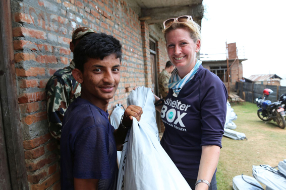 Becky Maynard (right) helps to distribute shelter kits to people in the remote area of Phataksila, Nepal.