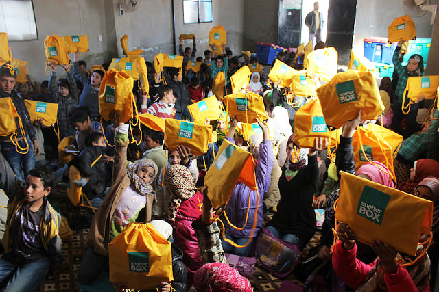 Syrian school children hold their Shelterbox activity pack aloft.