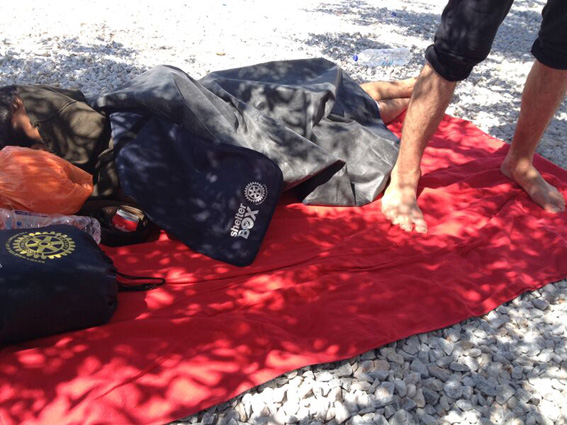 A man lies on a Shelterbox  blanket , cover by a Shelterbox ground mat