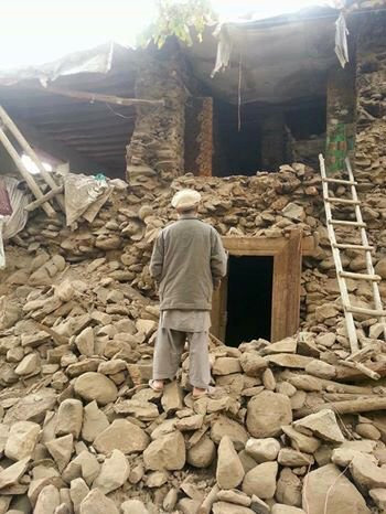 Image of Afghan man in front of collapsed building