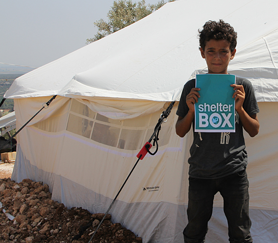 Young Syrian boy holding a ShelterBox sign in from of tent