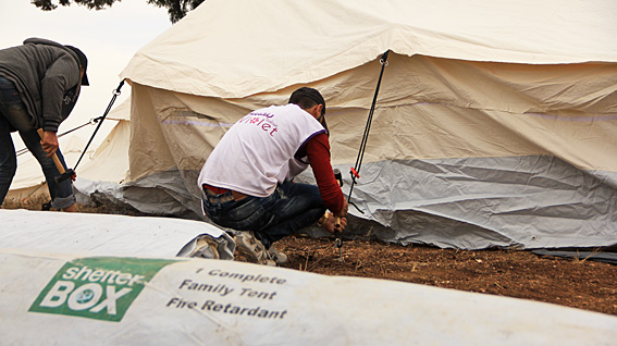 Volunteers from the Violet organisation erect tents donated by ShelterBox