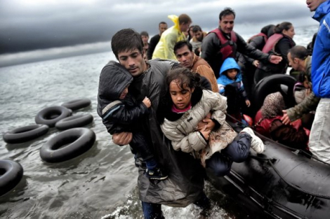 Refugees disembark an inflatable boat on the shores of Lesbos, a man carries two children to shore