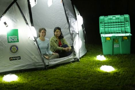 Inventors of the Luminaid solar light inside a Shelterbx tents in Malawi, surrounded by glowing Luminaids