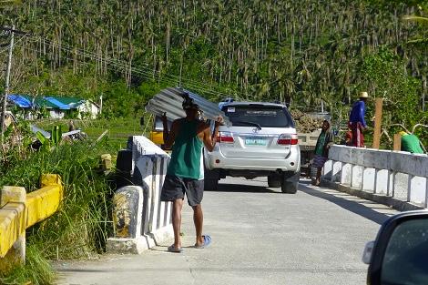 Filipino man carrying a corrugated iron sheet