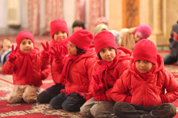 Syrian children wrapped in fleece coats, hats, gloves and scarves