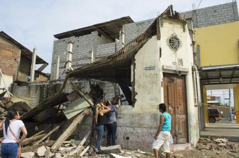 people taking photos of damaged church in Ecuador