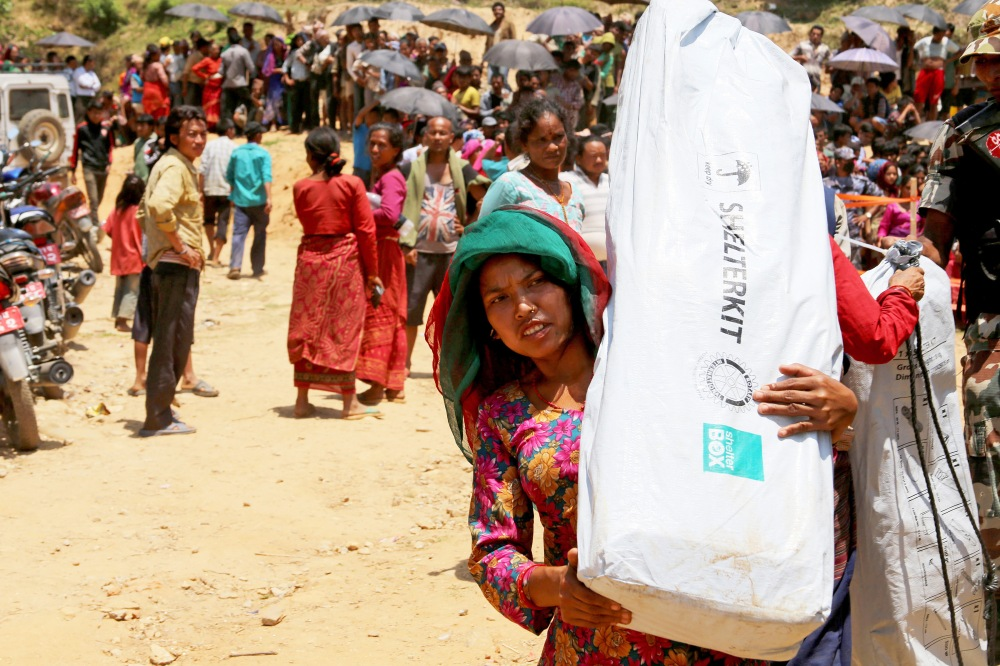 Nepali woman with shelter kit on her shoulder