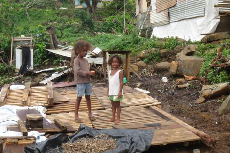 Children play in the reamins of a house on the island of Ovalau, Fiji