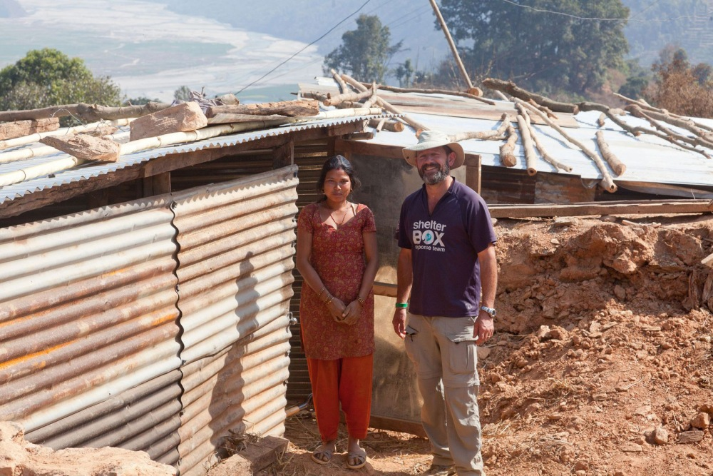 Surya and ShelterBox response team member Mike Greenslade stand outside her new home.