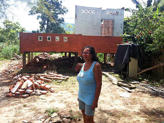 Image of a Maria outside her collapsed home
