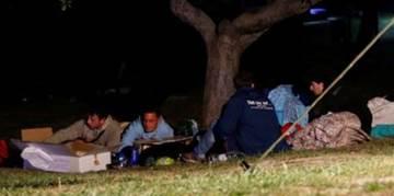 People sleeping outside under a tree