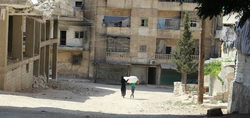 A Syrian mother and her child carry a shelter kit in the streets of Aleppo