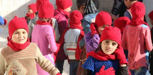 Iraqi children wearing red ShelterBox hats, scarves and gloves